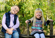 Happy Little Kids Sitting on a Wooden Garden Fence
