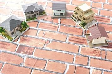 住宅模型とレンガの壁