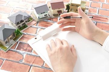 住宅の設計とメモをとっている営業マンの手