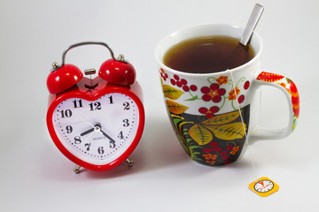 alarm clock and tea in a mug