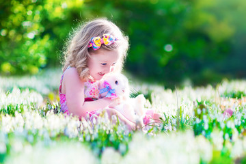 Sweet little girl playing with a rabbit