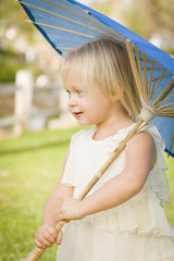 Cute Baby Girl Holding Parasol Outside At Park