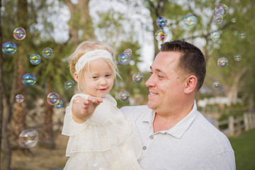 Father Holding Baby Girl Enjoying Bubbles Outside at Park