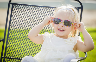 Cute Playful Baby Girl Wearing Sunglasses Outside at Park