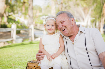 Grandfather and Granddaughter Hugging Outside At The Park