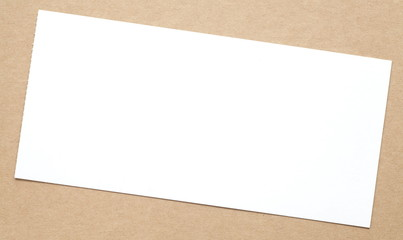 Blank white paper note on brown paper background