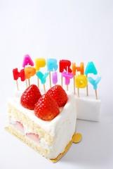 HappyBirthdayの文字のロウソクとイチゴのケーキ