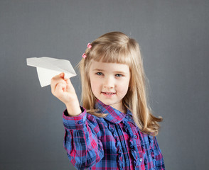 Smiling little girl flying paper plane