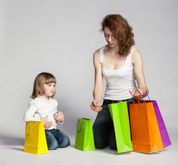 Little girl with her mother looking inside shopping bags