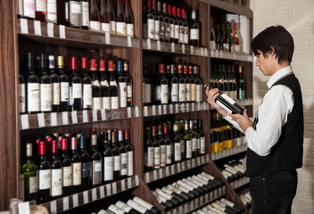 man looking at bottle of wine in shop. wine shopping