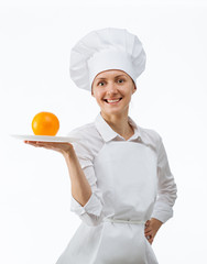 Beautiful young female cook showing orange on a plate