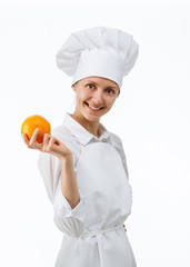 Beautiful young female cook showing an orange