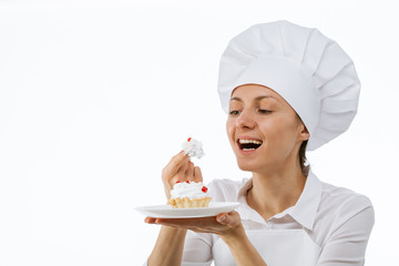 Young chef cook tasting a cake