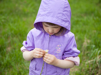 Little girl playing with a flower