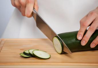 Female hand cutting zucchini on wooden board