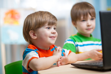 happy kids looking at laptop