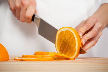 Female hands cutting fresh juicy orange