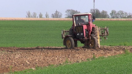 small old agriculture tractor cultivated field soil in spring