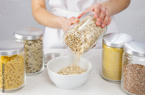 Female hands holding a pot with raw oatmeal