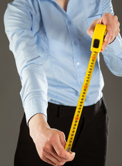 Unrecognizable young woman holding a tape measure