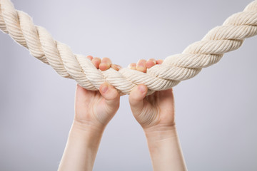 Hands of little girl hanging on a rope