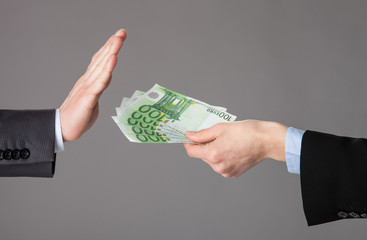 Businessman's hands rejecting an offer of money