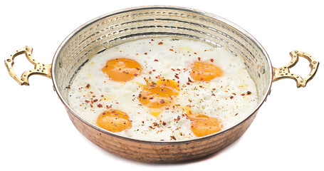 Fried egg in copper egg pan isolated on white background.