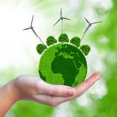 Green planet with trees and wind turbines in hand.