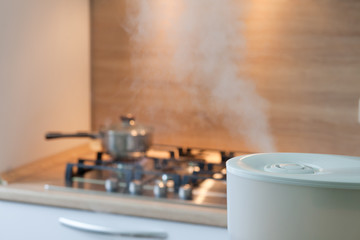 Humidifier spreading steam into the kitchen with pan on the oven