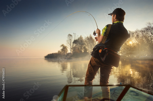 Young man fishing at misty sunrise - 79016603