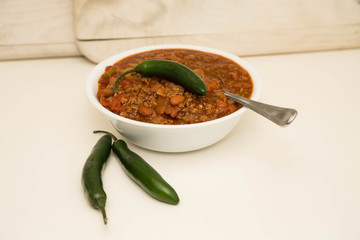 White Bowl of Chili with Two Jalapenos and One on Top