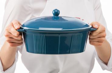 Female cook holding blue ceramic pan