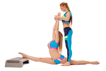 Beautiful girls doing stretching exercise in pair