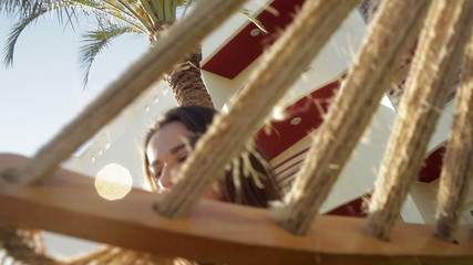 girl in a striped T-shirt sitting in a hammock