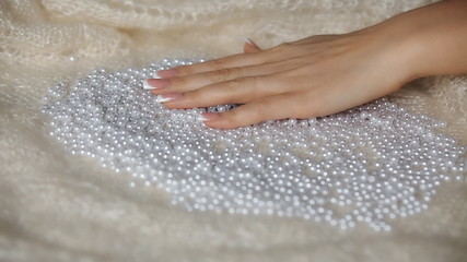 female hand touches pearls