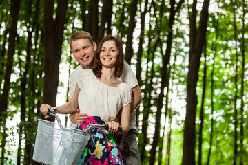 Happy beautiful young couple on bicycle