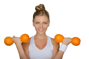 young girl holding dumbbells from ripe oranges