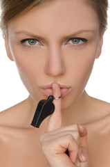 young woman holding finger and whistle before lips