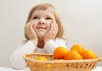 Smiling little girl with tangerines