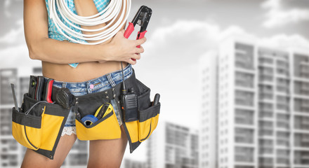 Woman in tool belt holding cable and pliers. Buildings with gray