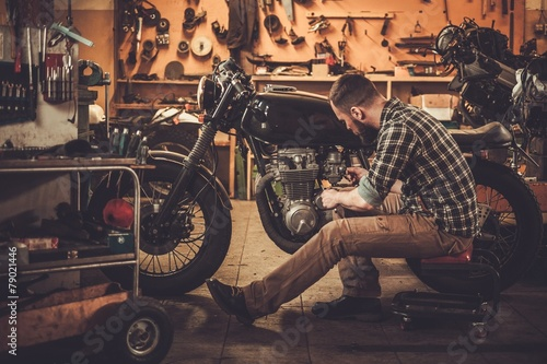 Mechanic building vintage style cafe-racer motorcycle   - 79021446