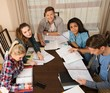 Students preparing for exams in home interior behind table