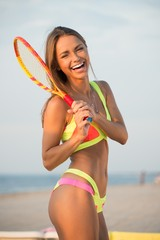 Young girl in swimming suit on a beach with racquet