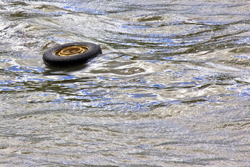 Abandoned tire flows into a river with copy space