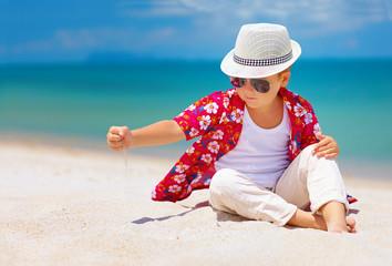 stylish kid, boy playing with sand on summer beach