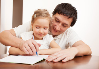 Father helping daughter doing homework