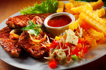 Grilled Meat with Fries and Veggies on Plate