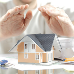 Conceptual Hands Over Miniature House on the Table