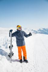 Happy skier sportsman at winter ski resort panoramic background