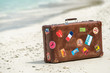 Travel vintage suitcase is alone on a beach - 79030490